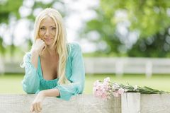 Junge blonde Frau durch den Zaun Stockfotografie