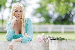 Junge blonde Frau durch den Zaun Lizenzfreies Stockfoto