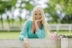 Junge blonde Frau durch den Zaun Stockfotos