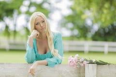 Junge blonde Frau durch den Zaun Lizenzfreie Stockfotos