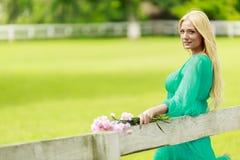 Junge blonde Frau durch den Zaun Lizenzfreies Stockbild