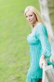 Junge blonde Frau durch Zaun Lizenzfreie Stockfotos