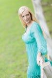 Junge blonde Frau durch Zaun Lizenzfreies Stockfoto