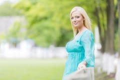 Junge blonde Frau durch Zaun Stockfotos