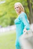 Junge blonde Frau durch Zaun Lizenzfreie Stockfotografie