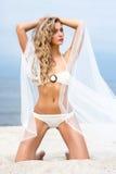 Junge blonde Frau in einem Badeanzug, der auf dem Strand aufwirft Lizenzfreie Stockfotografie