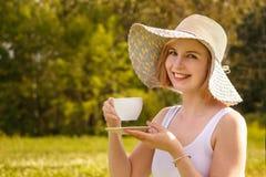 Junge blonde Frau in einem hellen Hut mit einer weißen Tasse Tee auf der Natur Stockbild