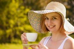 Junge blonde Frau in einem hellen Hut mit einer weißen Tasse Tee auf der Natur Stockfotografie