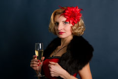 Junge blonde Frau in einem roten Kleid auf einem schwarzen Hintergrund Lizenzfreie Stockbilder