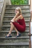 Junge blonde Frau in einem roten Kleid, das auf der Treppe stationiert und am Handy spricht Stockfoto