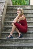 Junge blonde Frau in einem roten Kleid, das auf der Treppe stationiert und am Handy spricht Stockbild