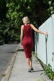 Junge blonde Frau in einem roten Kleid, das am Bretterzaun sich lehnt Lizenzfreies Stockfoto