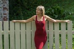 Junge blonde Frau in einem roten Kleid, das am Bretterzaun sich lehnt Stockbilder
