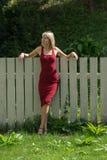 Junge blonde Frau in einem roten Kleid, das am Bretterzaun sich lehnt Stockfotos