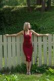Junge blonde Frau in einem roten Kleid, das am Bretterzaun sich lehnt Stockfotografie