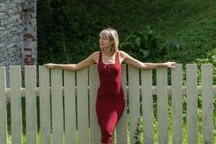 Junge blonde Frau in einem roten Kleid, das am Bretterzaun sich lehnt Lizenzfreie Stockfotos