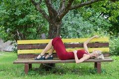 Junge blonde Frau in einem roten Kleiderlehnen sitzt auf einer Holzbank Stockbilder