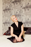 Junge blonde Frau in einem schwarzen Kleid, das auf dem Bett sitzt Stockfoto