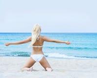 Junge blonde Frau in einem weißen Badeanzug auf dem Strand Stockbilder