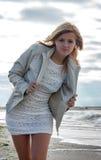 Junge blonde Frau in einem weißen Kleid mit der drapierten Jacke, die auf dem sandigen Strand gegen das Meer aufwirft Stockbilder