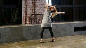 Junge blonde Frau führt in der grauen Kleidung nahe durch Fenster durch stock footage