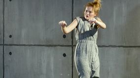 Junge blonde Frau führt in der Graukleidung nahe Wand durch stock video footage