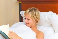 Junge blonde Frau im Bett Stockfoto