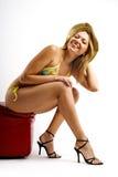 Junge blonde Frau im Bikini, der auf rotem Puff sitzt Lizenzfreie Stockfotografie