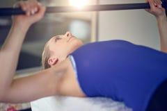 Junge blonde Frau im blauen Spitzenhandelnbankdrücken Stockbilder