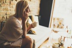 Junge blonde Frau im Café Stockbild