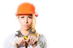 Junge blonde Frau im Erbauersturzhelm, der Schlüsselwerkzeug hält Lizenzfreie Stockbilder