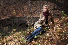 Junge blonde Frau im Herbstwald Lizenzfreies Stockfoto