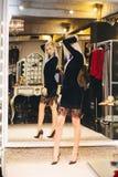 Junge blonde Frau im Kleid, das am großen Spiegel aufwirft Stockfotografie
