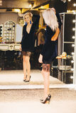 Junge blonde Frau im Kleid, das am großen Spiegel aufwirft Lizenzfreies Stockfoto