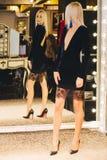 Junge blonde Frau im Kleid, das am großen Spiegel aufwirft Lizenzfreie Stockbilder