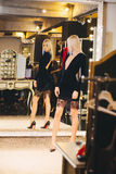Junge blonde Frau im Kleid, das am großen Spiegel aufwirft Stockfoto