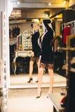 Junge blonde Frau im Kleid, das am großen Spiegel aufwirft Lizenzfreies Stockbild