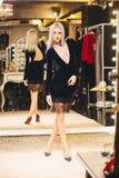 Junge blonde Frau im Kleid, das am großen Spiegel aufwirft Stockbild