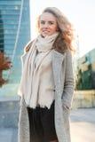 Junge blonde Frau im langen Mantel, der unter Gebäuden steht Stockfotografie