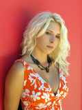 Junge blonde Frau im orange Kleidrothintergrund Stockfoto