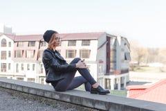 Junge blonde Frau im Schwarzen entspannt sich am Rand des Dachs im Stadtzentrum Lizenzfreie Stockbilder
