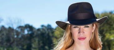 Junge blonde Frau im schwarzer Hut-heraus Tür-Porträt Stockbild