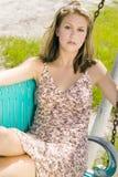 Junge blonde Frau im Sommerkleid, das auf einer Bank sitzt Lizenzfreies Stockbild