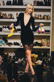 Junge blonde Frau im stilvollen Kleid wählt Schuhe Lizenzfreie Stockfotografie
