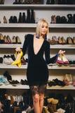 Junge blonde Frau im stilvollen Kleid wählt Schuhe Lizenzfreie Stockbilder