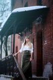 Junge blonde Frau im weißen Hemd, das unter dem alten Dach bleibt Stockbild