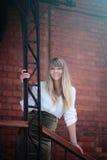 Junge blonde Frau im weißen Hemd, das unter dem alten Dach bleibt Lizenzfreie Stockfotos