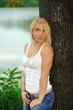Junge blonde Frau im weißen Trägershirt und in den Jeans Stockbild
