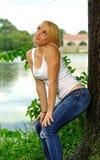 Junge blonde Frau im weißen Trägershirt und in den Jeans Lizenzfreies Stockfoto