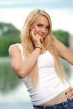 Junge blonde Frau im weißen Trägershirt und in den Jeans Lizenzfreie Stockfotografie